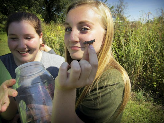 Caitlyn Jones (right) assists Paige Mirin with a grasshopper. Submitted - Lebanon Daily News