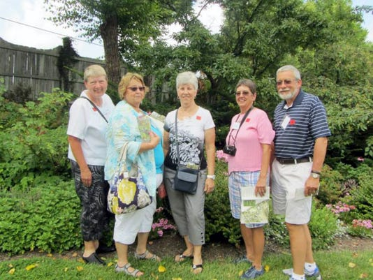 Sharon O'Connell, Donna Hake, Brenda Shearer, and Karen and Kevin Baum stand on the grounds of the Ladew Gardens.