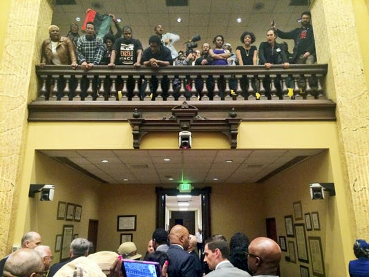 Protesters shout as council members leave the chamber at city hall in Baltimore, Wednesday, Oct. 14, 2015. A city council subcommittee voted to make Kevin Davis the permanent police commissioner Wednesday. (Colin Campbell/The Baltimore Sun via AP)