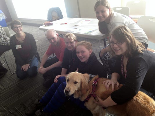 Shippensburg University students Abigail Cox, left, Sam Conely-Vaverchak, Heather Ritter, Devon Donahue, Vanessa Thomas and Morgan Mellott gather Tuesday around 'Dotty,' a therapy dog during a Home@Ship session on the SU campus. Students who are homesick are welcome to spend time petting dogs and meet new people during the program sessions.