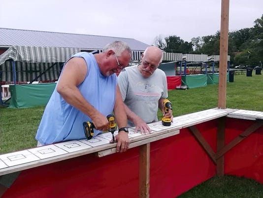Alan Behm, left, and Nip Bernard  are both members of the festival set-up crew for Sacred Heart Church. They are shown here putting finishing touches on a booth for the upcoming festival. Marylouise Sholly -- Lebanon Daily News