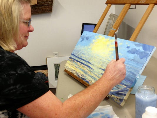 Local artist Kristine Tebay paints a landscape at her Market View Arts studio. The West Philadelphia Street studio features local artists, some of who do their work in the building.