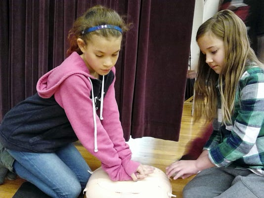 South Lebanon Elementary School fifth-graders Mariah Haggerty, left, and Chloe Hains demonstrate their CPR skills during a recent assembly.