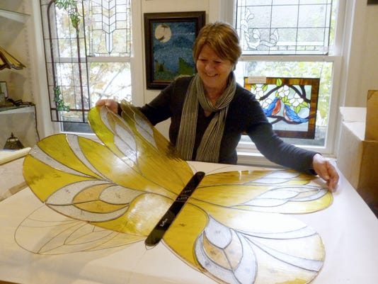 Luise Christensen-Howell displays one of the glass butterflies, measuring 32-by-37 inches, that she made for the conservatory currently under construction at Hershey Gardens.