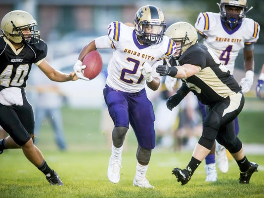 Union City running back Taj Reid (21) runs between Delone Catholic's Andrew Hernandez (40) and Trey Reese (55) during Friday's game in McSherrystown. Reid rushed for 14 yards and returned a blocked field goal attempt for a touchdown to help the Golden Tornadoes win, 56-0.