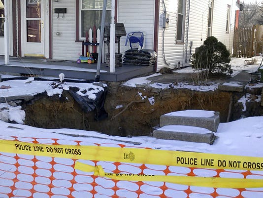 Snow rings a growing sinkhole in front of 302 E. Cherry St. in Palmyra this week. It's one of three that forced the evacuation of several homes in October. Borough officials soon hope to meet with residents to discuss options for repairing sinkholes in the neighborhood.
