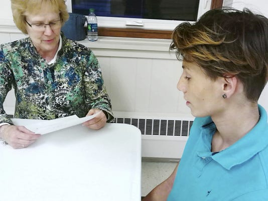 """Zion Evangelical Lutheran Church member Linda Toth asks a question of Julian Hernandez, 15, during a mock job interview at the Jonestown church. The exercise was part of the day treatment program of Youth Advocacy of Lebanon County. Church members like Toth volunteered to be """"interviewers"""" to guide the boys through the job application process."""