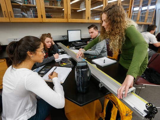 In a February 2018 general physics course, Lena Hamaker, right, stretches a spring as her classmates, from left, Lorena Velasquez, Andrea Leenerts, and Caleb Saab write down measurements. The class was learning about the forces that springs exert in combination so they could model how metals behave.