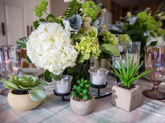 A flower bouquet and succulents sits on display at
