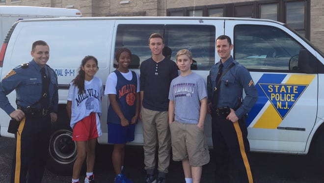 (From left) New Jersey State Police Trooper Victor Petrilli,  Katia Morales, Zi'anne Cunningham, Dominic Buonadonna, Dreu Ferus and Trooper Mark Campagna prepare for a coat giveaway that will be held Saturday at Millville Memorial High School.