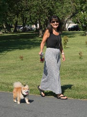 Dawn Baddock, an Animal Resource Foundation volunteer, walks with her Pomeranian dog, Lissie, on June 28, 2017. Lissie was a dog rescued from the high-profile Wicomico County puppy mill case.