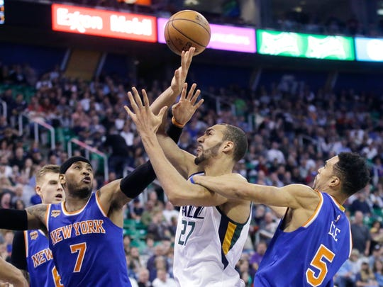 New York Knicks guard Courtney Lee (5) fouls Utah Jazz center Rudy Gobert (27) as Knicks forward Carmelo Anthony (7) defends during the second half of a game Wednesday, March 22, 2017, in Salt Lake City. The Jazz won 108-101.