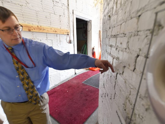 Sevastopol School Superintendent Kyle Luedtke points out a significant crack beginning from the floor and traveling up at least 30 feet inside the boiler room built in 1924 at Sevastopol School.