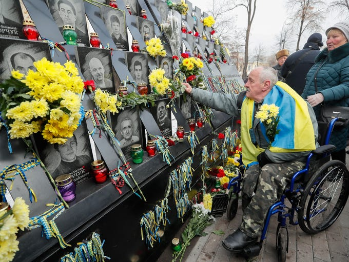 Ukrainians lay flowers at the memorial for Maidan activists