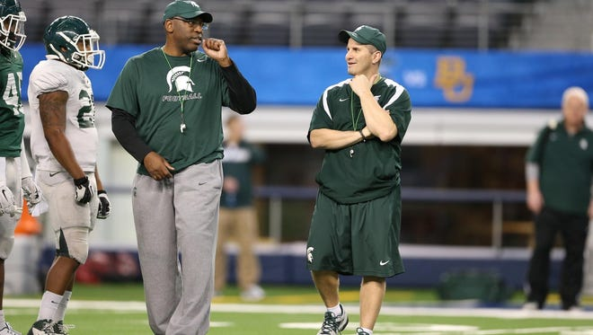 MSU secondary coach Harlon Barnett, left, and linebackers coach Mike Tressel, right, talk during Saturday's Cotton Bowl practice. Together, they're being promoted to co-defensive coordinator, replacing Pat Narduzzi.