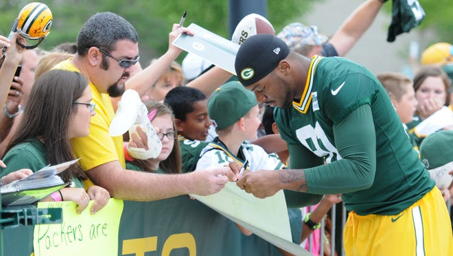 Green Bay Packers linebacker Jayrone Elliott signs autographs during training camp practice at Ray Nitschke Field, Thursday, August 21, 2014.