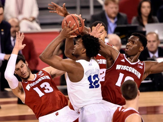 Apr 6, 2015; Indianapolis, IN, USA;  Duke Blue Devils forward Justise Winslow (12) drives to the basket against Wisconsin Badgers forward Duje Dukan (13) and forward Nigel Hayes (10) during the second halfin the 2015 NCAA Men's Division I Championship game at Lucas Oil Stadium. Mandatory Credit: Jamie Rhodes-USA TODAY Sports