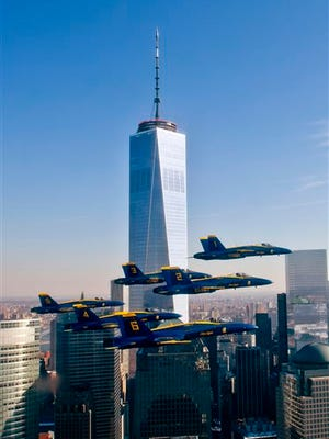 This Dec. 13, 2013 photo taken by the U.S. Navy, shows the Blue Angels during a performance near the One World Trade Center in New York. An elite group of Navy and Marine photographers are selected each year to travel the world with the U.S. Navy Blue Angels flight demonstration team. The photographers often ride with pilots and must be in top physical condition to make the team and have the skills to capture aerial maneuvers at speeds of up to 700 miles per hour. (Terrence Siren/U.S. Navy via AP)