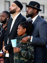 Imam Omar Suleiman, center, The Rev. Dr. Michael W. Waters, right, and his son Jeremiah, stand in attendance at a candle light vigil for Jordan Edwards, in Balch Springs, Texas, Thursday, May 4, 2017. Solemn and Waters were featured speakers at the event that drew a few hundred supporters.