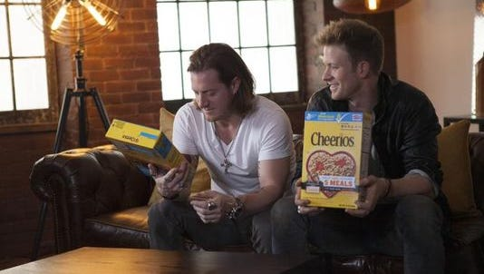 Members of Florida Georgia Line look at their Cheerios boxes for the first time in February.