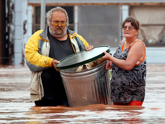 George and Susan Kruger make one of three trips with their animals from their flooded house to safety on Sunday in Purcell, Okla. Water from overnight rains began to rise early in the morning.  That storm system is entering Arkansas, creating a number of weather watches by the National Weather Service.
