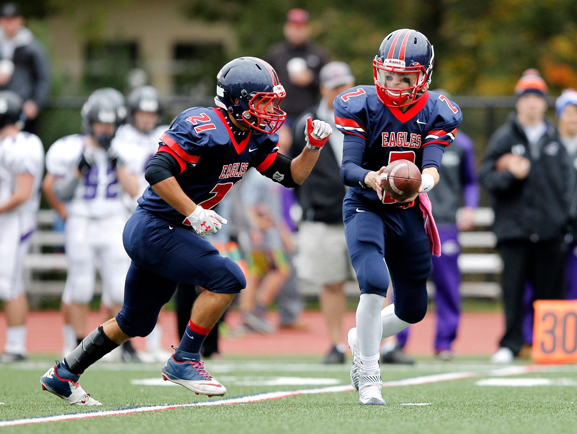Eastchester quarterback John Archidiacono (2) hands off to Michael Cesarini (21) during a varsity football game against John Jay Cross River at Eastchester High School on Saturday, Oct. 24, 2015.