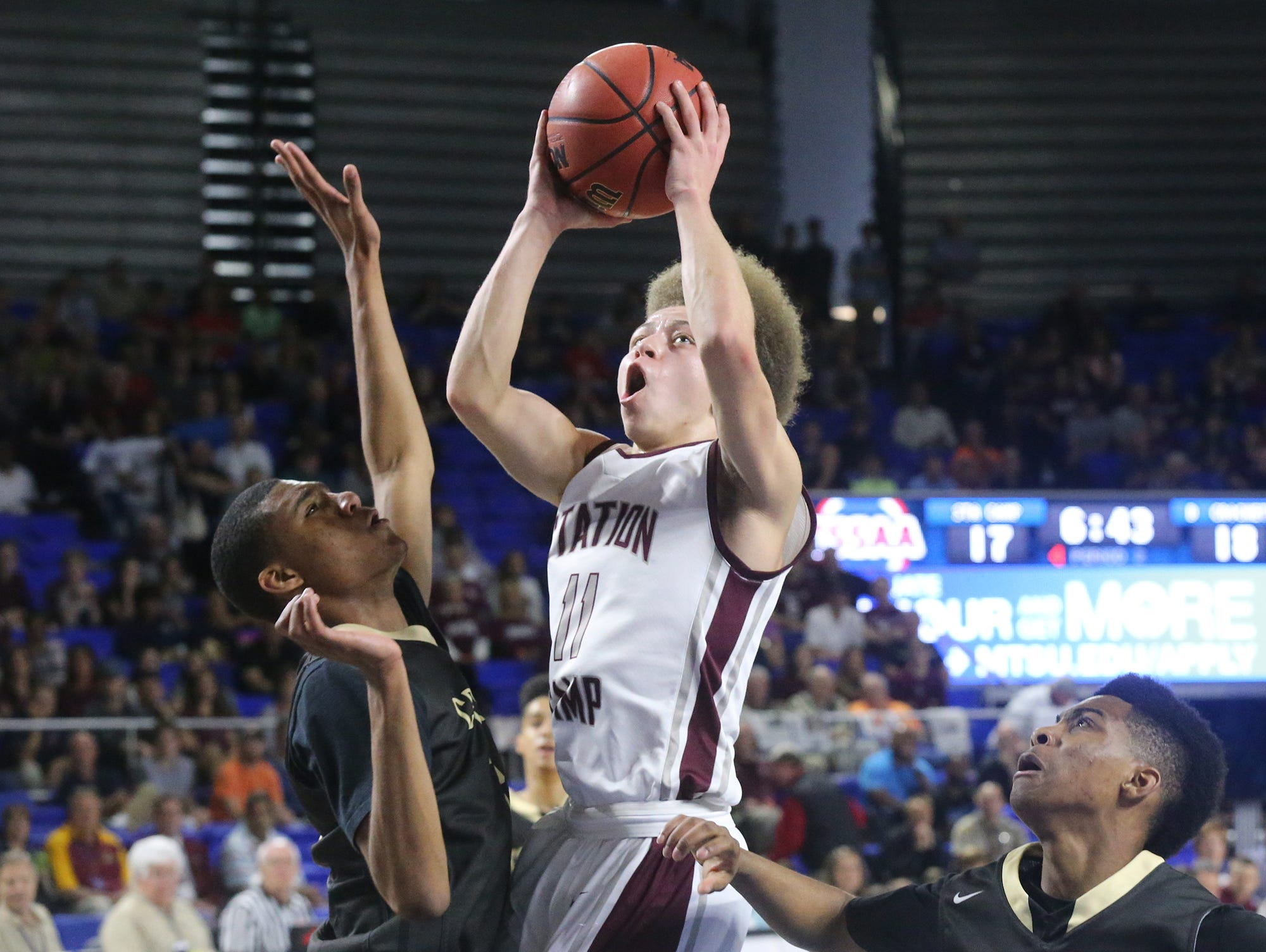 """Station Camp's Chase Freeman (11) goes up for a between David Crockett""""s Brendan Coleman (24) and Darian Delapp (14) during the Class AAA boys state quarterfinals at MTSU's Murphy Center Wednesday."""