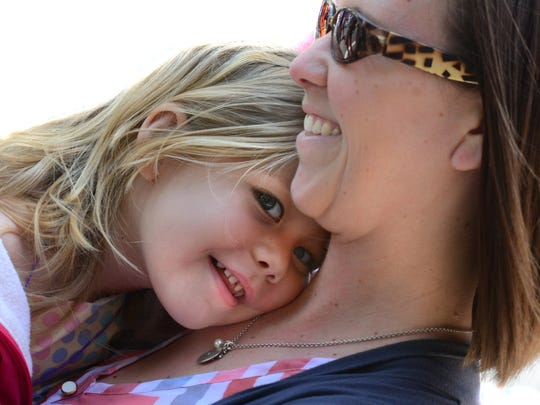 Addison Leakway, 3, of York gets a hug from her mother Nicole at the 41st annual Olde York Street Fair that attracted near-record crowds Sunday, May 8, 2016. Bil Bowden photo