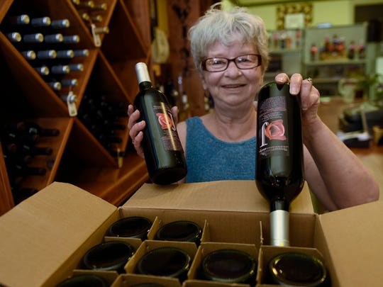 Sue Hadley stocks shelves with wine Friday, June 30,