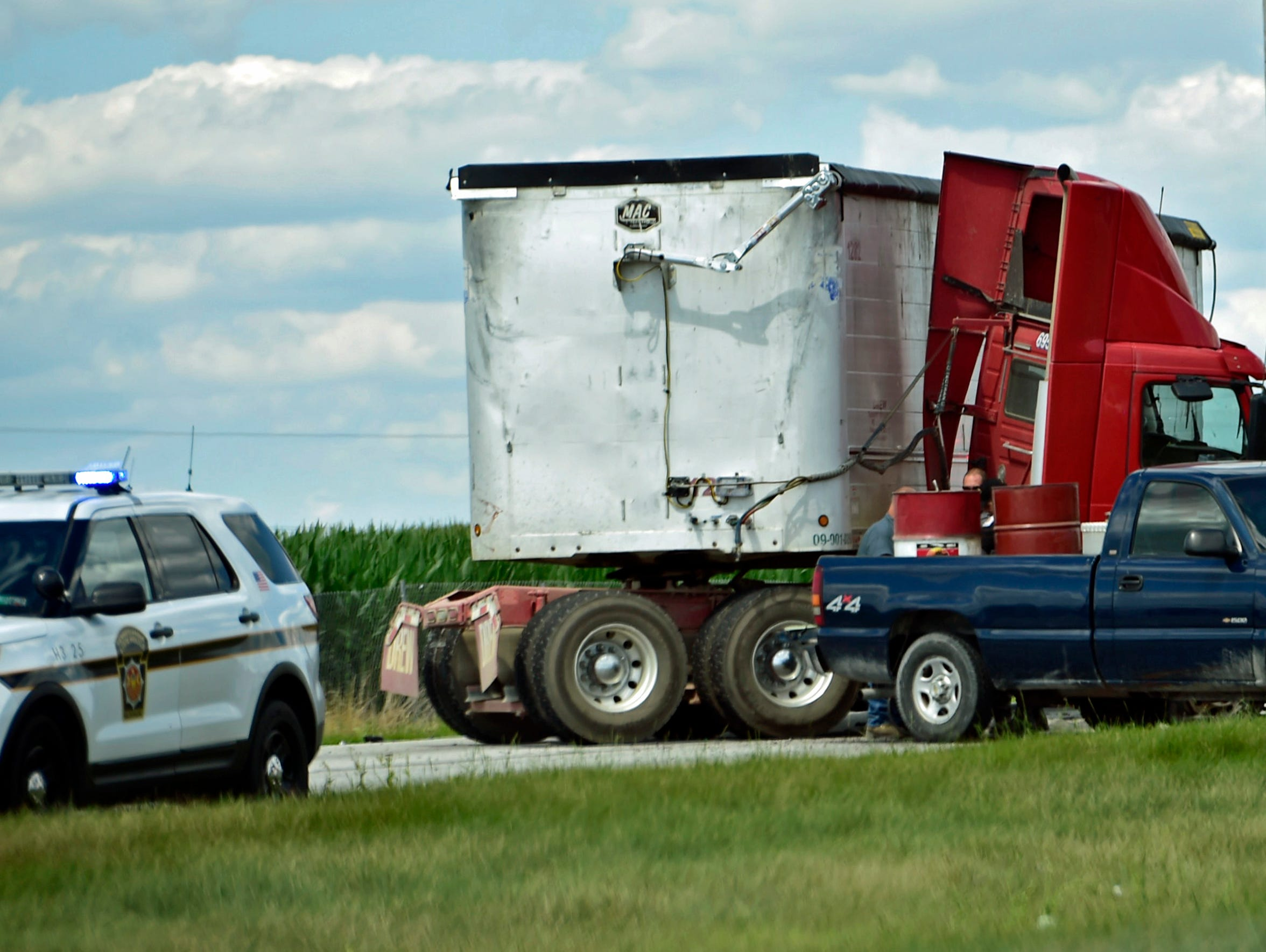A jack-knifed tractor-trailer sits in the southbound