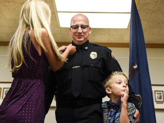 Madisyn Breiner (left) and Alex (right) pin on their father's, Todd Breiner, police chief's insignia after Lebanon Mayor Sherry Capello announced Breiner would be the new chief of police in the Lebanon City Police Department and Lt. Dave Gingrich would be promoted to captain in city council chambers on Monday, July 18, 2016.