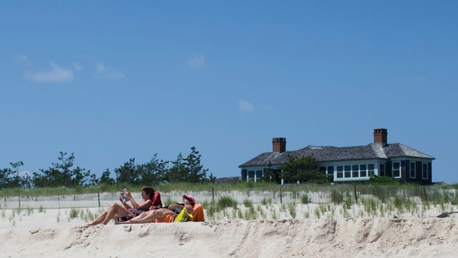 Beachgoers relax near a property in Southampton. Studies show the gap separating the rich from the working poor has been widening in recent years and few places provide that evidence as starkly as Long Island's Hamptons.
