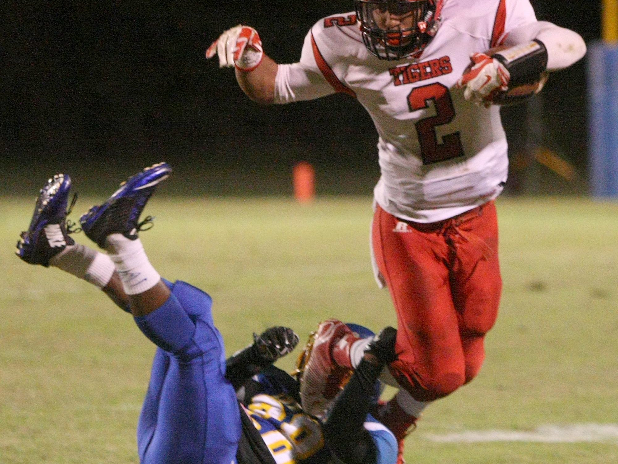 Lexington's Camrion Hollingsworth (2) is brought down by North Side's Randall Boyington (28) on Friday at North Side.