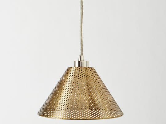 This photo provided by West Elm shows a pendant fixture in a pierced warm metallic that would make a pretty accent light for a kitchen island or entryway. Pierced metal is one of the stronger style points for this fall and winter. (AP Photo/West Elm)