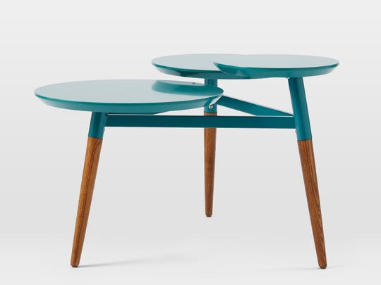 This photo provided by West Elm shows a Clover coffee table that takes an iconic midcentury shape and offers it in a variety of finishes, including teal blue. It is also available in red.