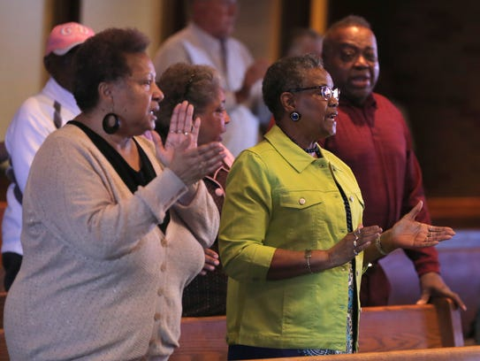 Worshipers gather and sing during Good Friday services