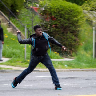 A demonstrator throws a rock at police after the funeral