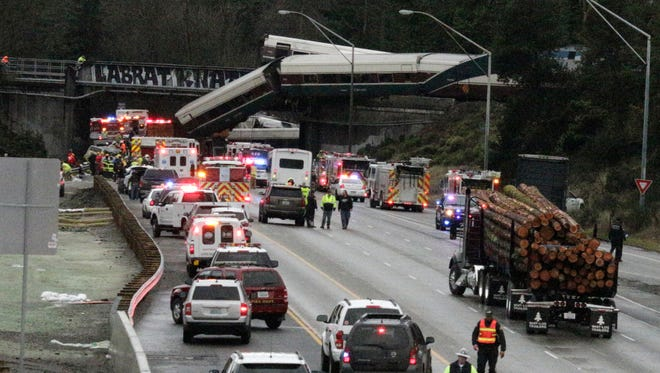 A derailed Amtrak train is seen on southbound Interstate 5 on Monday in DuPont, Wash.