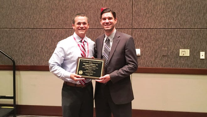 Jason Vaughn, left, presents Simpsonville's Shawn Goddeyne with the South Carolina Society of Professional Engineers' Young Engineer of the Year Award for 2016.