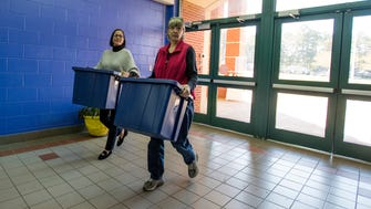 Nelya McKenzie, right, and Nancy Jo Brown, left, deliver backpack food bags for Holy Comforter Church to Fitzpatrick Elementary School in Montgomery, Ala. on Friday November 17, 2017.