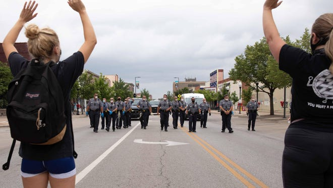 The Lawrence Police Department and Douglas County Sheriff's Office move toward individuals who refused to relocate from Massachusetts Street on Monday afternoon. Protesters have occupied the downtown street for multiple days after a graphic, racially charged banner was discovered nearby Saturday denouncing the Black Lives Matter movement.