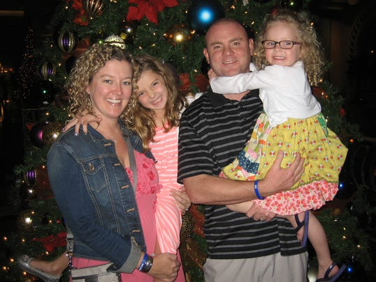Butler University assistant men's basketball coach Michael Lewis with wife, Nichole, and daughters Avery and Emma (right).