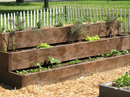 This three-tiered raised beds offers herbs and strawberries.