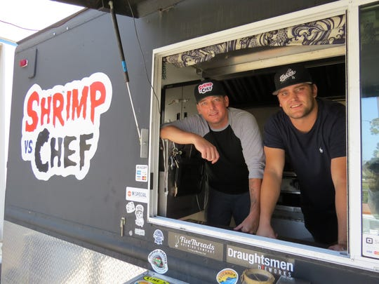 Temple Sewell, executive chef and owner of the Shrimp vs. Chef food truck, poses in the order window with chef Dillion Cappello.