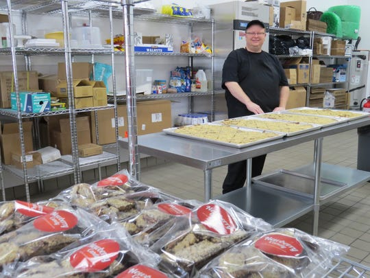 Newberry Candy owner John Newberry poses with trays of in-progress toffee in the kitchen of the Thousand Oaks business. Packages of toffee made according to his late mother's recipe are seen in the foreground.