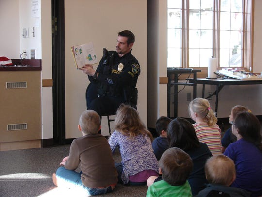 Stayton Police Officer Jason Meeker reads during a Dr. Seuss party
