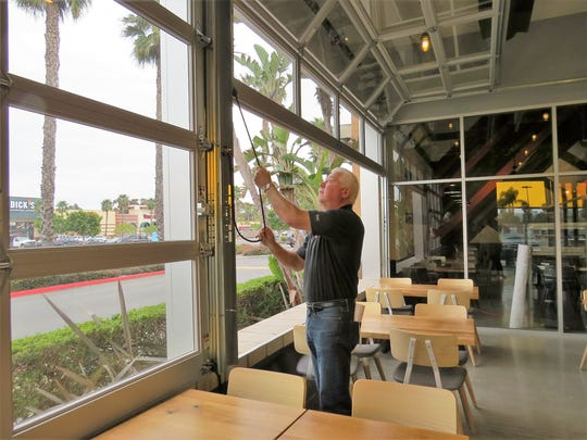 Scott Soller, operations director for H.R. Pizza Holdings LLC, operates the roll-up patio doors at Blaze Pizza in Oxnard's Esplanade Shopping Center. The restaurant will open to the public on March 2.