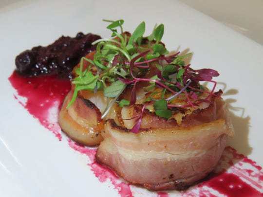 An appetizer of pan-seared, bacon-wrapped scallops