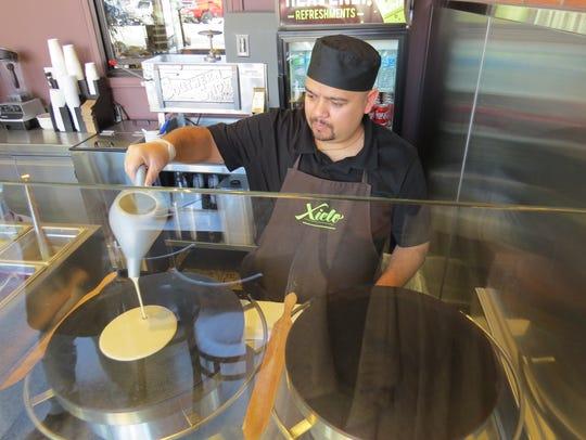Chef Roberto Maravilla pours crepe batter at Xielo