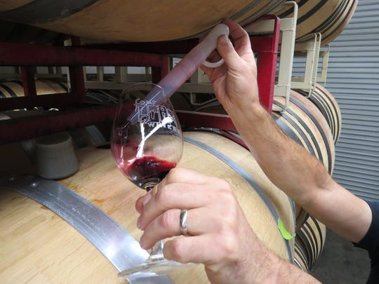 Four Brix Winery vintner Gary Stewart uses a wine thief to draw a tasting straight out of an oak barrel. Similar barrel tastings will be available June 16-17 during a passport event at eight Ventura County wineries — Four Brix among them.